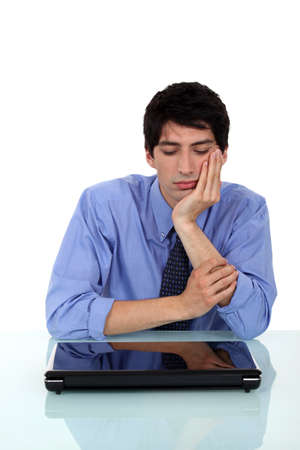 hesitancy: Bored man sat by closed laptop Stock Photo