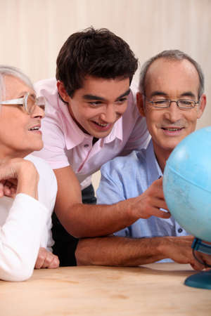 grandparents ant their grandson looking at a globe photo