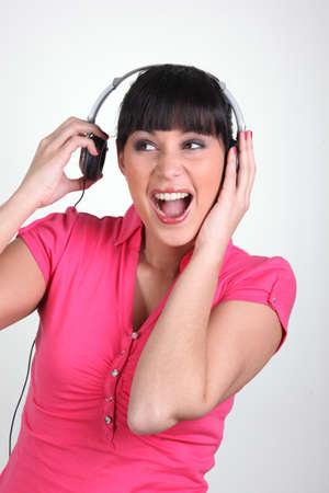 splitting up: Brunette listening to loud music through headphones