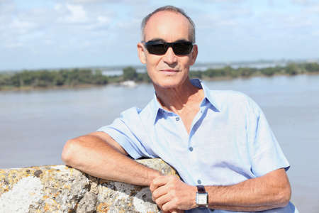 65 years old: 65 years old man in front of a river and some island