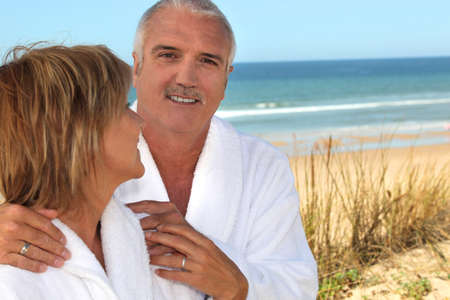 55 59 years: Mature woman gazing lovingly at her partner in the sand dunes Stock Photo