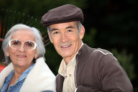 Elderly couple with garden rake photo