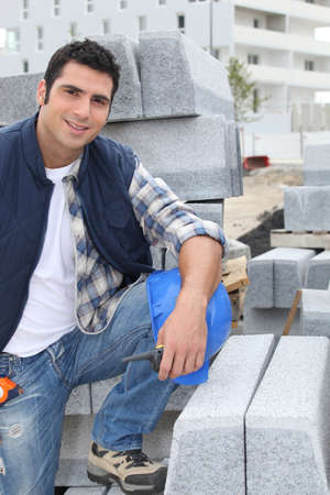 cement pile: Worker posing with stacks of concrete blocks