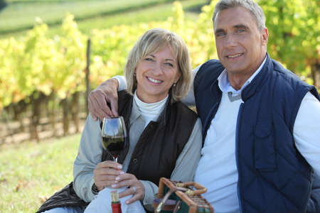 men 45 years: Couple tasting wine in a vineyard Stock Photo