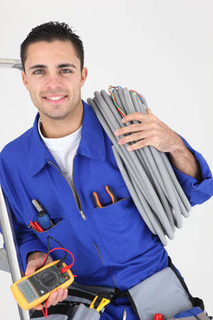 Worker carrying cabling coiled around his shoulder photo