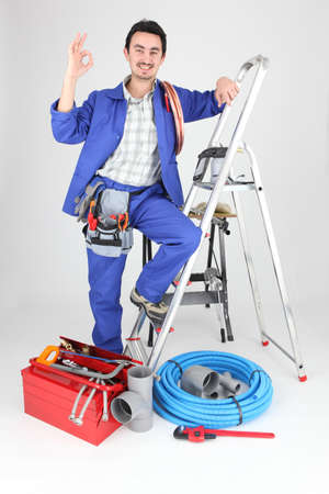 Man with ladder and plumbing tools photo