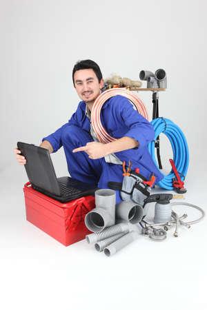 plumber kneeling showing computer photo