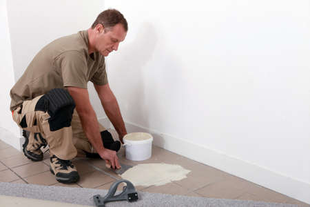 Carpet fitter applying adhesive over an old tiled floor