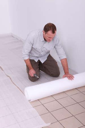 Man unrolling underlay Stock Photo - 10783604