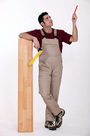 planking: portrait of carpenter with parquet looking upwards Stock Photo