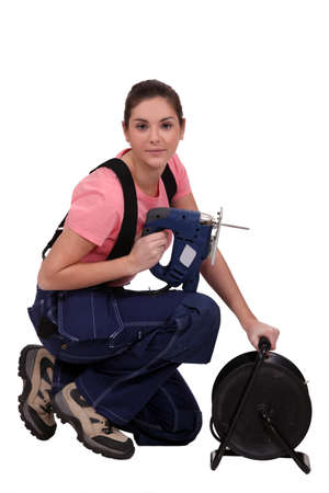 Handywoman holding a jigsaw and an extension cord photo