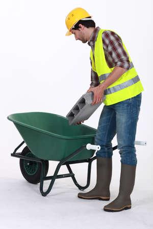 Worker putting a concrete block into a wheelbarrow photo