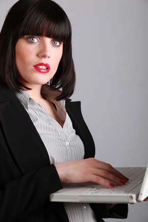 Woman in red lipstick working at a laptop computer photo
