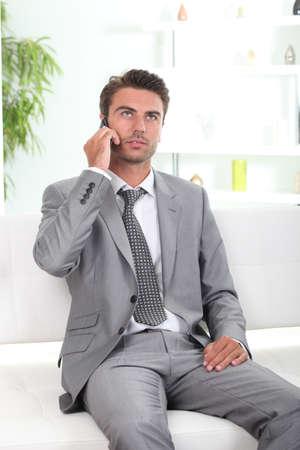 Bored executive on a cellphone Stock Photo - 10783646