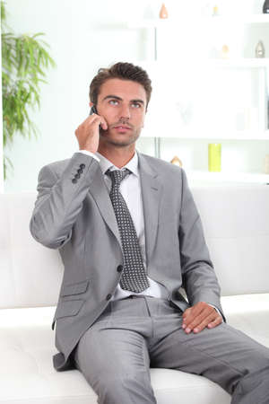 Bored executive on a cellphone Stock Photo - 10783646