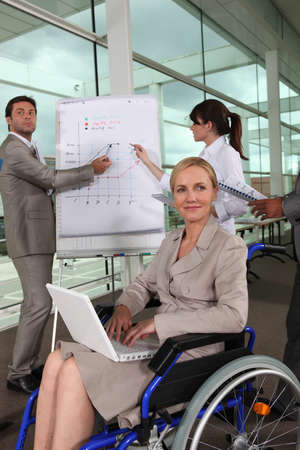 Female executive in wheelchair using laptop computer during presentation Stock Photo - 10783536