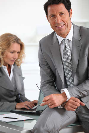 Businessman sat on desk photo