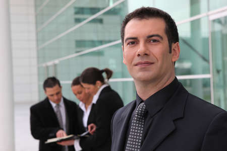 Confident businessman and business team outdoors Stock Photo - 10783469