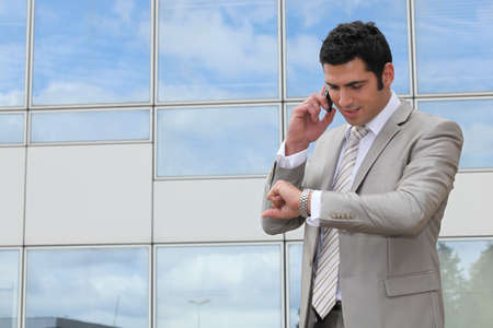 Businessman outside looking at watch photo