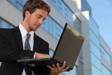 25 29 years: Young executive using a laptop outside an office building Stock Photo