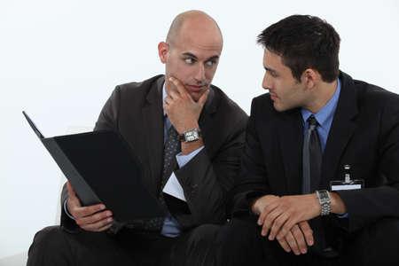 conferring: Businessmen discussing a file