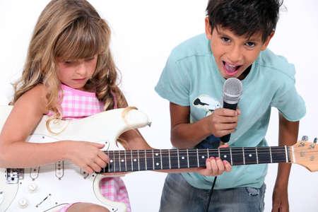 cantando: los niños cantando y tocando música Foto de archivo