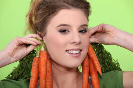 Woman wearing carrots as earrings Stock Photo - 10783591