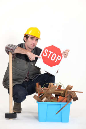 impede: Labourer holding a stop sign while squatting before a bin full of wood