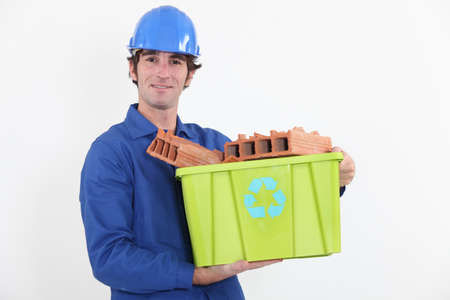 portrait of bricklayer in jumpsuit holding tub full of bricks with recycling logo photo