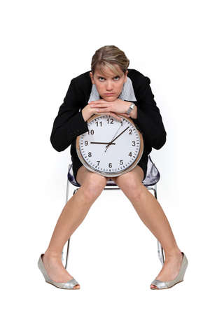 working stiff: Businesswoman sitting with a large clock