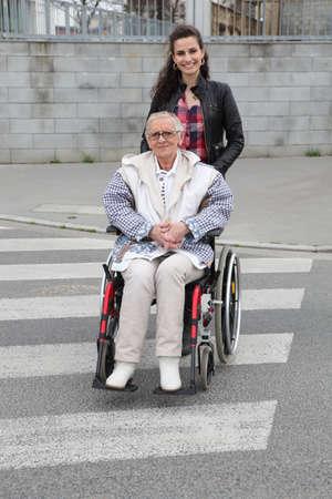 Girl pushing senior woman in wheelchair photo