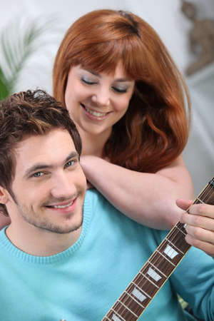 Young couple with a guitar at home Stock Photo - 10783652