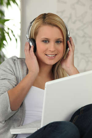Young girl listening to her laptop on headphones photo