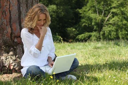 sat: Blond woman sat by tree with laptop