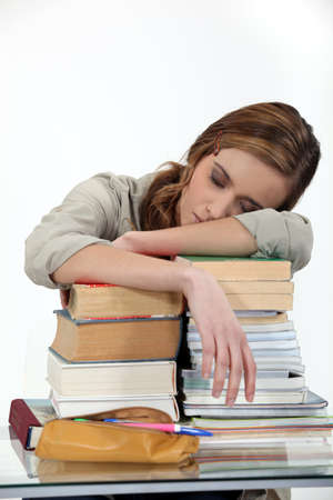 student sleeping over a pile of books photo