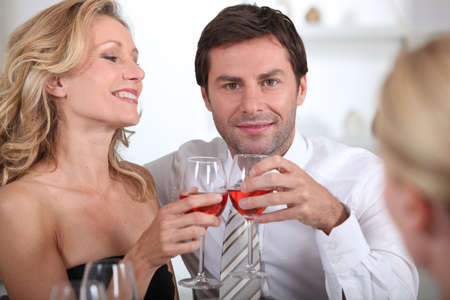invited: Couple sitting holding wine glasses together Stock Photo