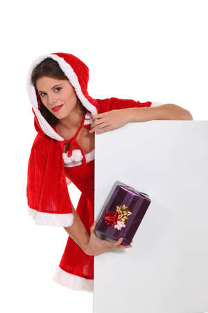 ms: Cute Ms Santa with a gift and a board left blank for your message Stock Photo