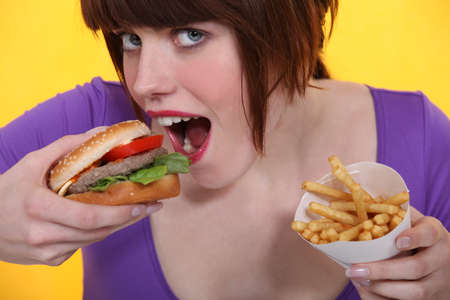 stuffing: Woman eating a burger and chips