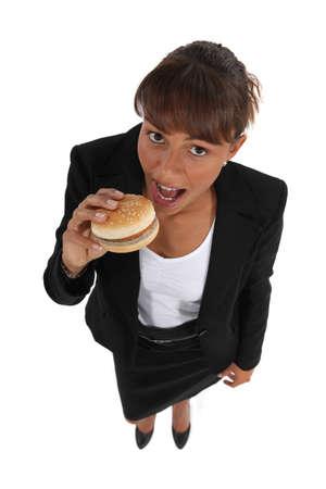 woman eating a hamburger Stock Photo - 10782273