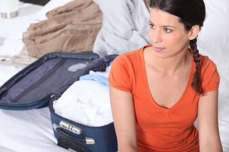 packing suitcase: Young woman packing a suitcase Stock Photo