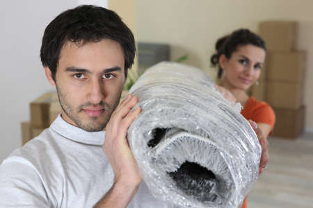 unemotional: Couple carrying a rolled-up rug Stock Photo