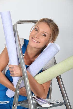 numerous: Woman  holding numerous wallpaper rolls