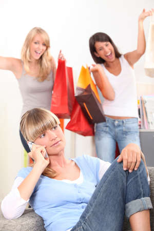 tedious: Young woman on the telephone as her friends walk in with bags of retail purchases