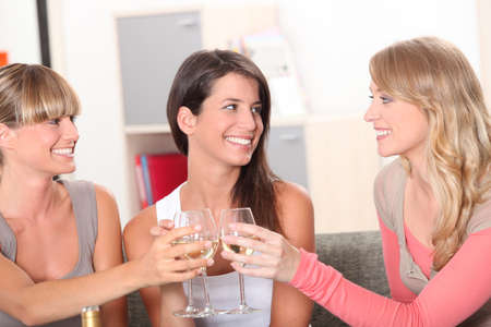 Three housemates drinking wine together Stock Photo - 10783599