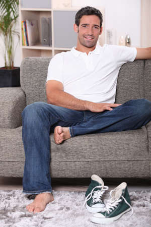 seating furniture: man sitting on a couch and smiling