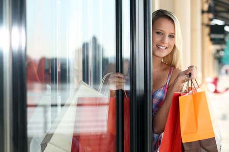 abriendo puerta: Mujer rubia que sale de la tienda de ropa