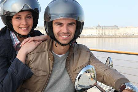 Couple riding scooter over bridge photo