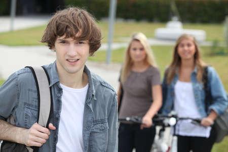 young man standing: Giovane uomo in piedi di fronte a due ragazze con le bici Archivio Fotografico