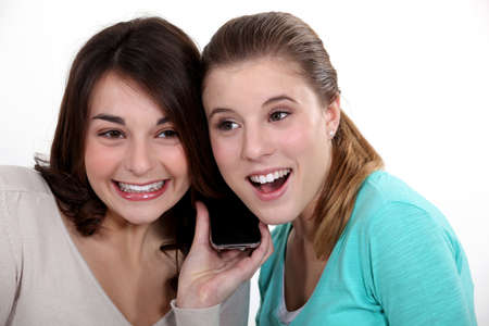 Women excitedly listening to a song Stock Photo - 10783614