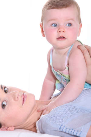 6 12: Mother playing with her baby girl on her chest Stock Photo